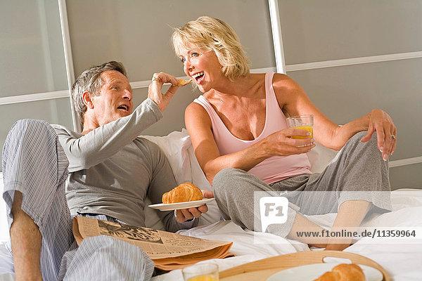 Romantischer älterer Mann füttert Frühstückscroissant an Frau im Bett