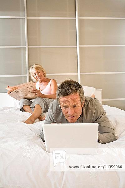 Paar auf dem Bett Zeitung lesen und mit Laptop