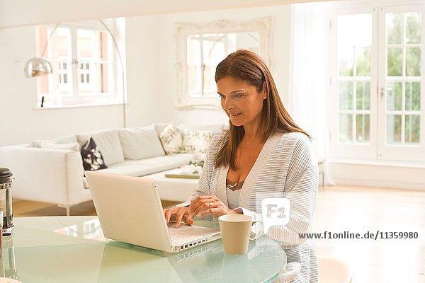 Reife Frau am Tisch beim Tippen auf dem Laptop