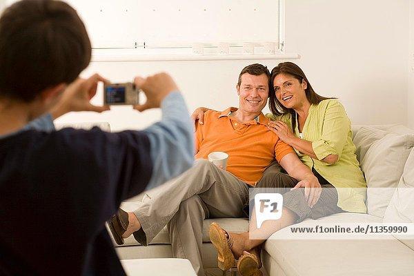 Junge fotografiert seine Eltern auf dem Sofa