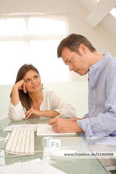 Reife Paare prüfen Rechnungen und erledigen den Papierkram auf dem Schreibtisch.