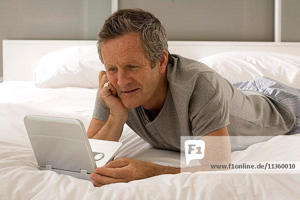 Verwirrter älterer Mann  der auf dem Bett liegt und auf den Laptop starrt.