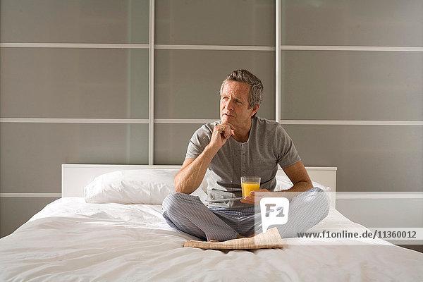 Verwirrter älterer Mann sitzend im Kreuzbein auf Bett mit Hand am Kinn