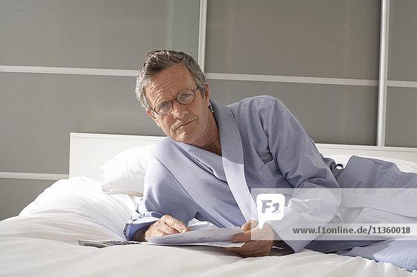 Porträt eines älteren Mannes  der auf dem Bett liegt und Rechnungen prüft.