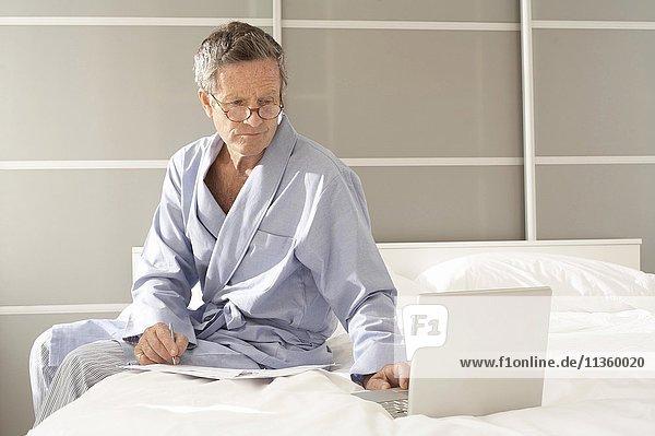 Senior Mann sitzt auf dem Bett und prüft Rechnungen auf dem Laptop.