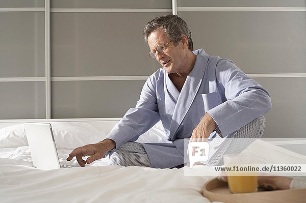 Verwirrter älterer Mann auf dem Bett  der auf dem Laptop schreibt.