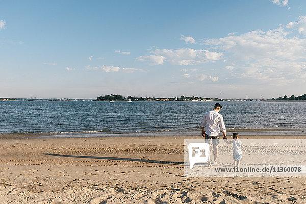 Rückansicht eines jungen Mannes  der mit seinem kleinen Sohn am Strand des Pelham Bay Park  Bronx  New York  USA  spazieren geht