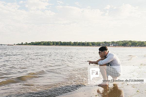 Junger Mann mit einem Kleinkind  das auf das Meer zeigt  Pelham Bay Park  Bronx  New York  USA