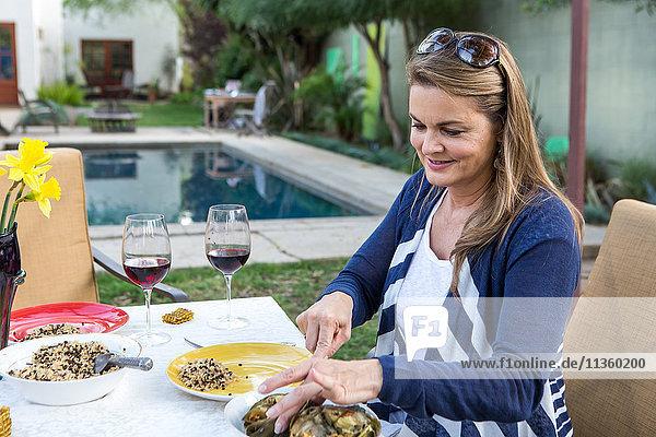 Reife Frau serviert Essen am Gartentisch