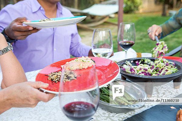Schnappschuss von Männern  die am Gartentisch Essen auf Tellern servieren
