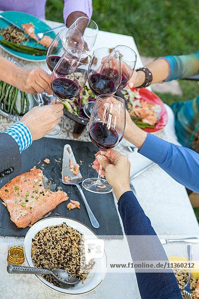 Hände reifer Freunde  die am Tisch der Gartenparty einen Rotwein-Toast ausbringen