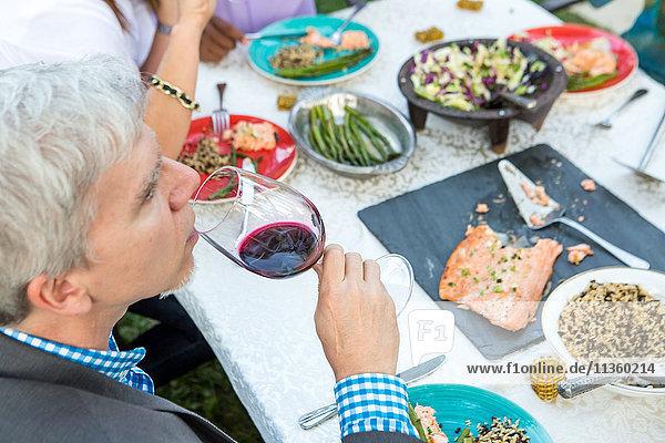 Über-Schulter-Ansicht von reifen erwachsenen Freunden beim Essen und Trinken am Gartenparty-Tisch