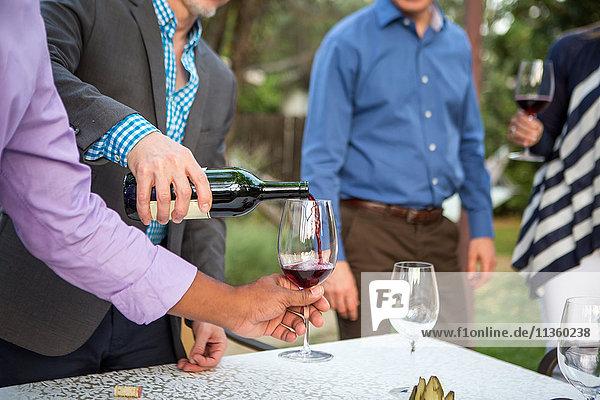 Männerhände gießen Rotwein am Tisch der Gartenparty
