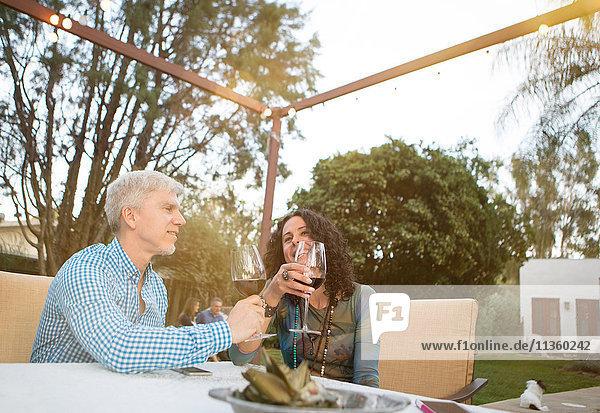 Reife Paare beim Plaudern und Rotweintrinken am Gartentisch