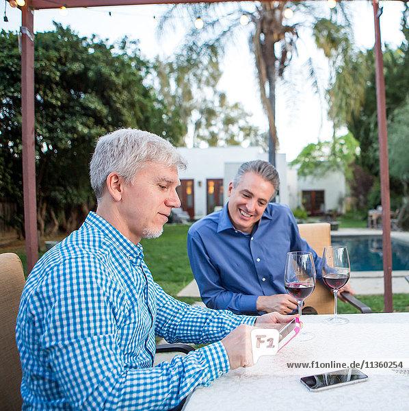 Zwei reife Männer schauen auf den Touchscreen eines Smartphones am Gartenparty-Tisch