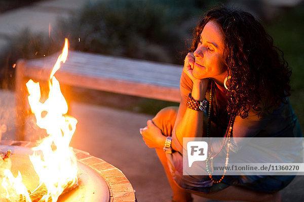 Reife Frau  die in der Abenddämmerung auf der Terrasse hockt und dem Feuer zuschaut