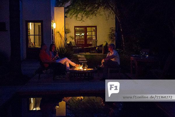 Reife Erwachsene entspannen sich in der Abenddämmerung am Terrassenfeuer