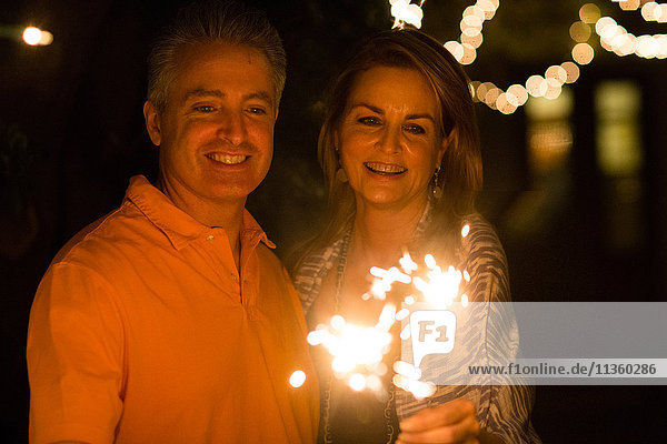 Ein erwachsenes Paar spielt nachts im Garten mit Wunderkerzen