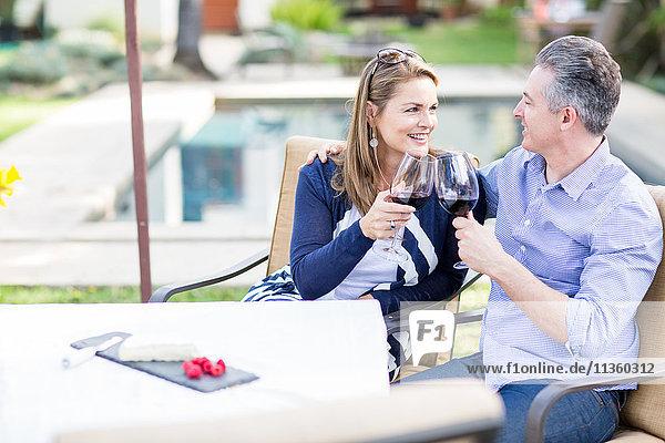 Romantisches reifes Paar beim Rotwein-Toast am Gartentisch
