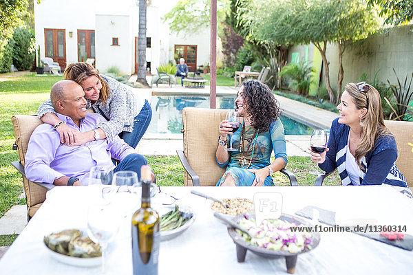 Reife erwachsene Freunde beim Plaudern am Gartenparty-Tisch