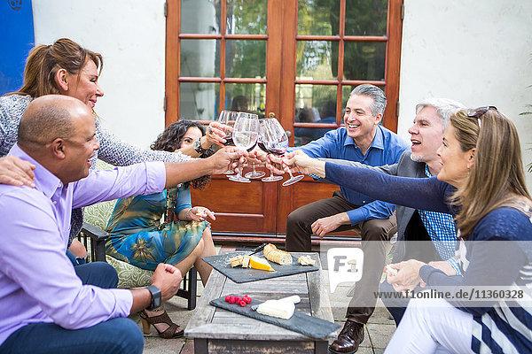 Sechs erwachsene Freunde machen Weintoast auf der Gartenparty auf der Terrasse.
