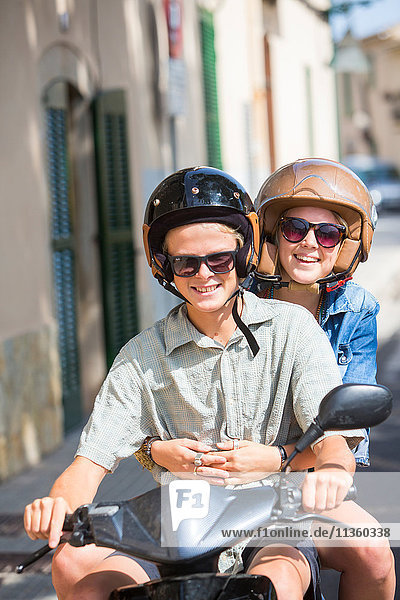 Young couple riding moped through village  Majorca  Spain