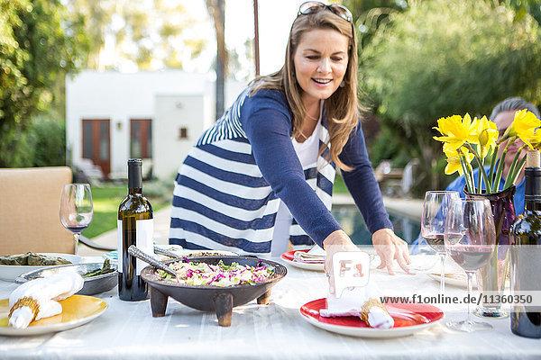 Reife Frau legt Servietten auf Gartenparty-Tisch