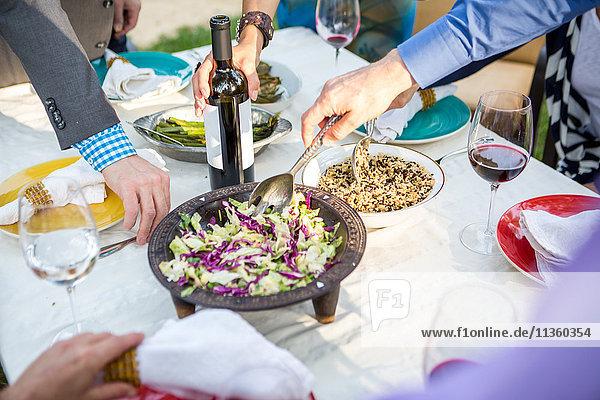 Ausschnitt eines Schusses von erwachsenen Freunden  die sich am Tisch der Gartenparty selbst essen und trinken