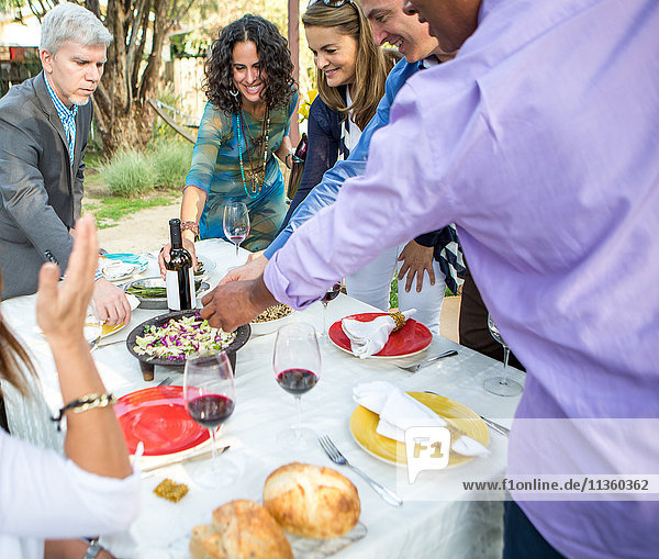 Erwachsene Freunde bedienen sich bei Essen und Trinken am Tisch der Gartenparty