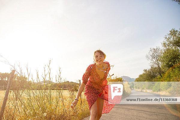 Glückliche junge Frau in rotem Kleid läuft auf Landstraße  Mallorca  Spanien