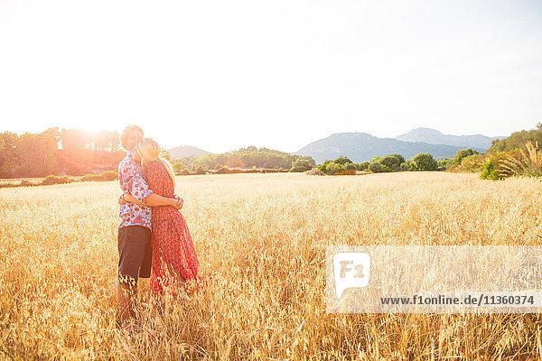 Romantisches junges Paar im Weizenfeld stehend  Mallorca  Spanien
