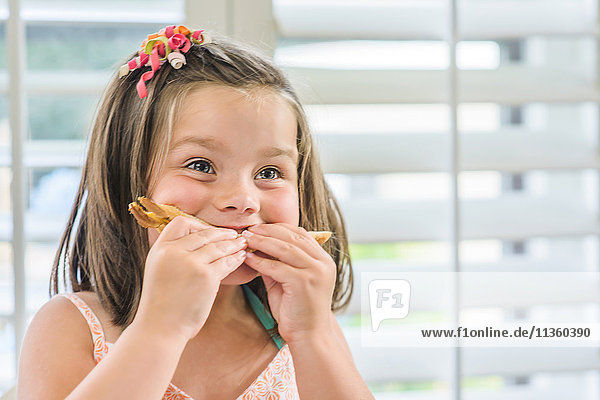 Cute girl eating sandwich in kitchen