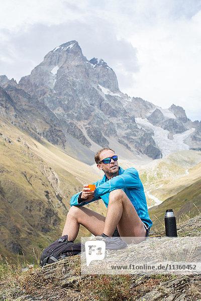 Männlicher Wanderer bei einer Kaffeepause in der Berglandschaft  Ushba  Svaneti  Georgien