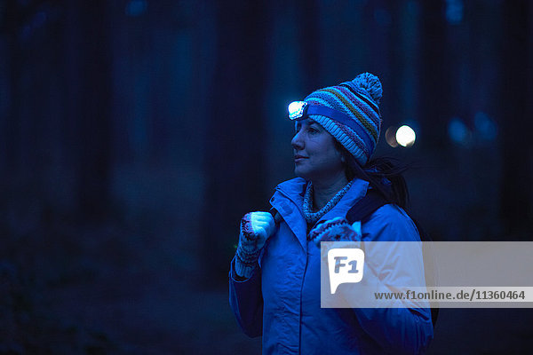 Female hiker wearing head torch hiking through forest at night