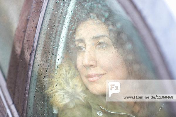 Reife Frau blickt bei Regen durch Autofenster