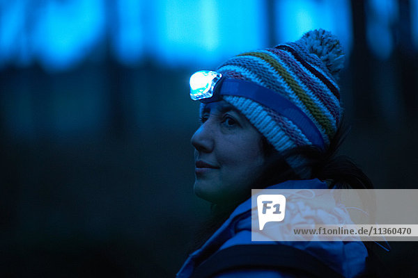 Weibliche Wanderin mit Stirnlampe  die nachts aus dem Wald über ihre Schulter schaut