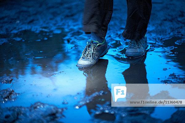 Füße einer Wanderin  die in eine schlammige Pfütze tritt