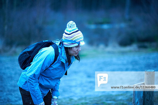 Female hiker wearing head torch reading in forest notice at dusk