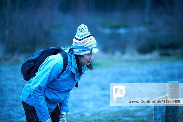 Wanderin mit Stirnlampe liest in der Dämmerung im Wald