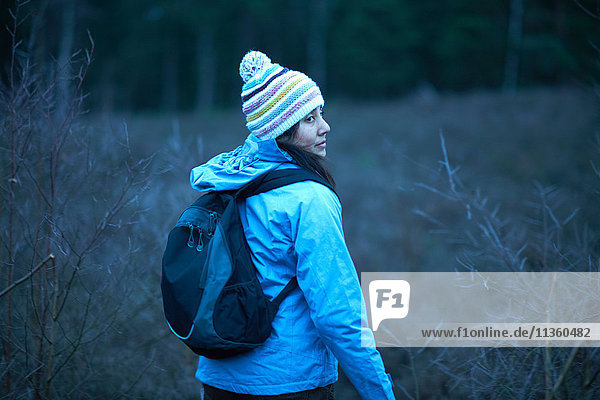 Female hiker looking back whilst hiking in forest at dusk