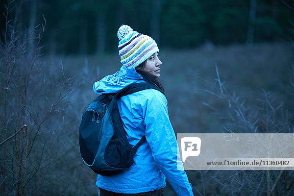 Wanderin blickt in der Dämmerung beim Wandern im Wald zurück