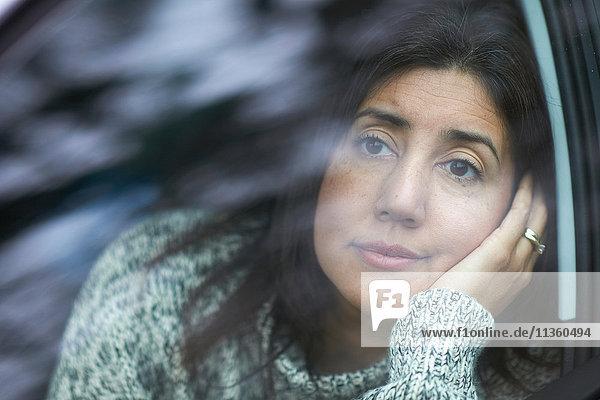 Reife Frau blickt durch Autofenster