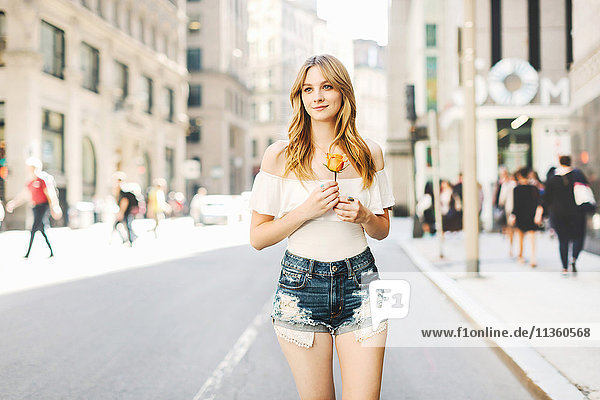 Porträt einer jungen Frau  die abgeschnittene Jeans-Shorts trägt  eine gelbe Rose hält und entlang der Straße geht