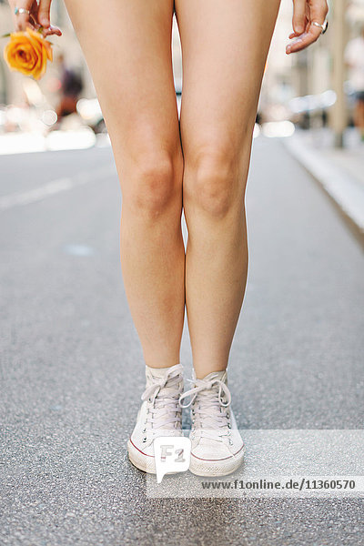Young woman standing in road  holding yellow rose  wearing baseball boots  low section