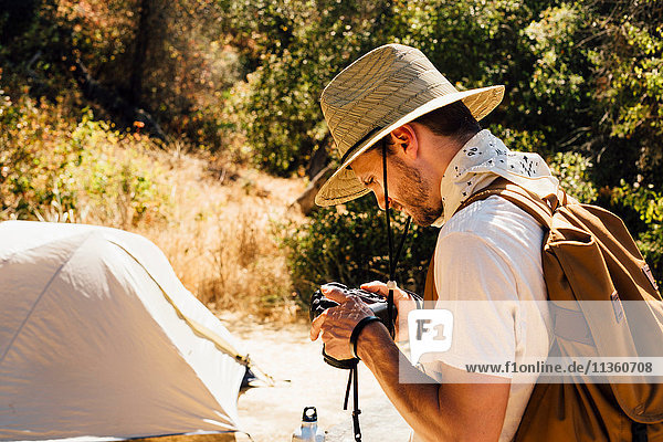 Man with camera by tent  Malibu Canyon  California  USA