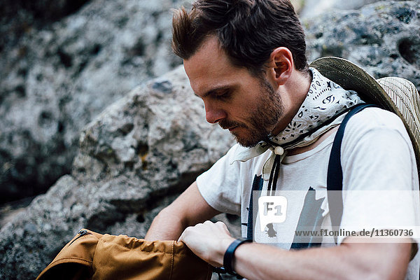 Hiker looking in backpack  Malibu Canyon  California  USA