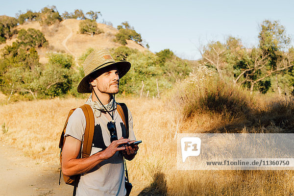 Hiker holding smartphone looking away  Malibu Canyon  California  USA