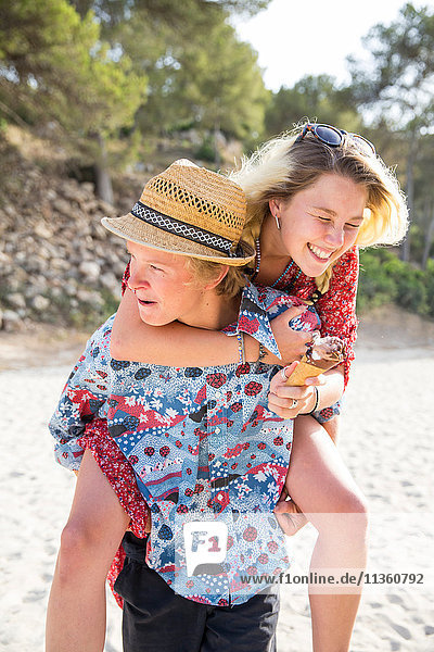 Mann am Strand gibt lächelnder Frau Huckepack  Mallorca  Spanien