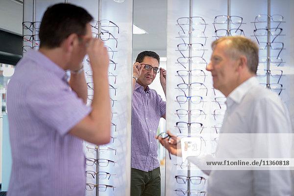 Kunden probieren Brillenfassungen bei Optikern für Kleinunternehmen an