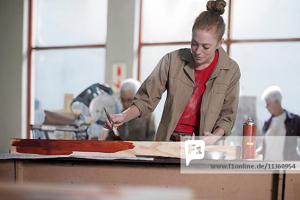 Young female carpenter painting wood stain in furniture making workshop